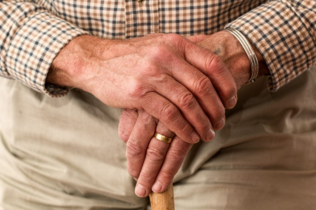 Hands of elderly person holding walking stick